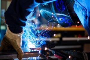 man working wearing a welding helmet