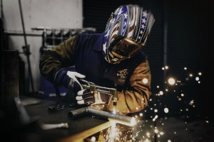 Welder leaning on the table doing work